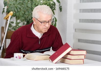 Older man with walking stick sitting in his home and reading books