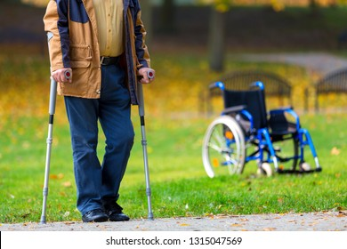 older man wearing moro trousers practicing walking on crutches in the park