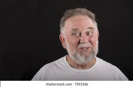 An older man in white tshirt looking to the right against black background
