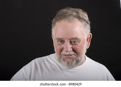 An older man in white tshirt on a black background looking down with an expressive face