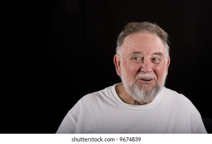 An older man in a white tshirt on black background smiling and looking to the left