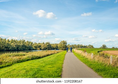 Older man and woman cycle on a curved cycle path on a dike on the edge of the Dutch National Park De Biesbosch. It is a sunny day with white clouds on the blue sky in the beginning of the fall season.