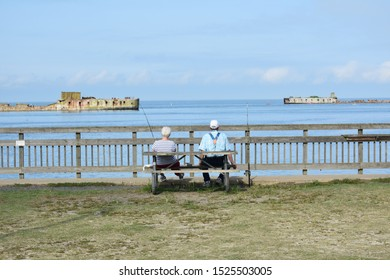 Older man and woman fishing on pier