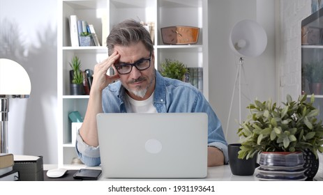 Older man working online with laptop computer at home sitting at desk. Home office, browsing internet, study room, entrepreneur.