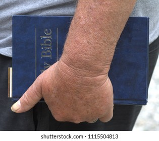 Older man's hand carrying a blue Bible