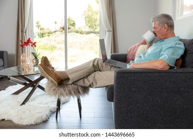 Older mature man relaxed on weekend morning, legs and feet up laid back with coffee and a laptop