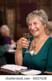 Older mature senior lady celebrating in posh restaurant
