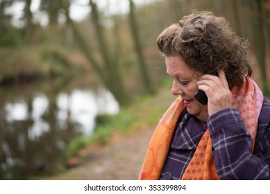 Older, mature woman. Calling on a cell phone while being outdoors. Nature. Bad news call. Sad.