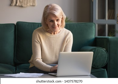 Older mature woman using wireless laptop apps browsing internet sit on sofa, smiling middle aged grandmother working distantly on computer surfing web communicating online looking at screen at home