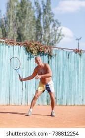 Older men hit the ball on the tennis court.