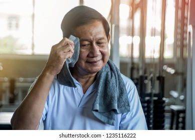 Older men sitting in the gym, tired of exercise, use a towel to wipe the sweat.