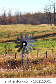 Older multi vane wooden windmill in the midst of fenced pasture land