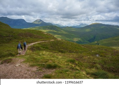Older people with backpacks walking along West Highland Way in Scotland under cloudy sky