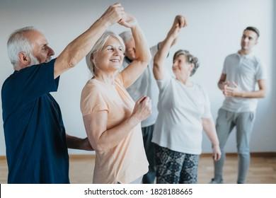 Ältere Menschen tanzen mit ihren Partnern auf einem Tanzkurs
