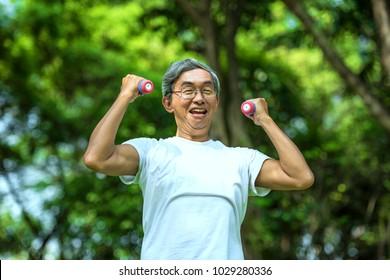 Older people are exercising healthy. Elderly man holding dumbbells. Soft focus concept.