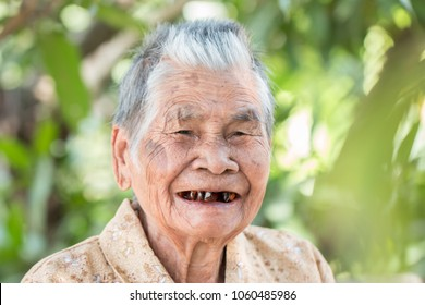 Older people for insurance concept : Portrait of Asian elder woman is smiling with her black tooth with happy at outdoor in sunny day