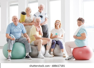 Older people smiling and posing for a photo at the gym