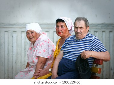 Older people: three Russian pensioners on a bench near the entrance of an apartment building. Russia, the city of Volgograd.