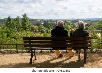 Older retired couple sitting on a bench and enjoy the view
