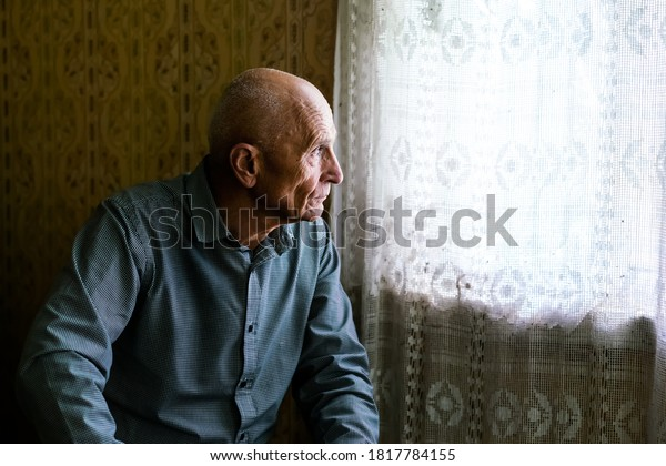 older sad bald man siting on sofa in village house and looking to window senior persons concept