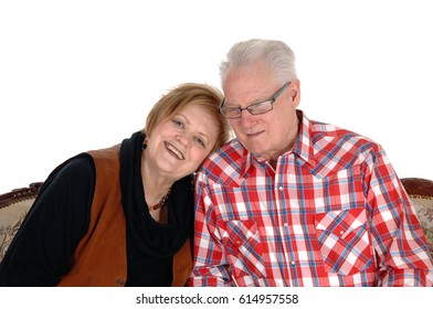 An older senior citizen couple sitting on a sofa, the wife with her headon the shoulder of her husband, isolated for white background.