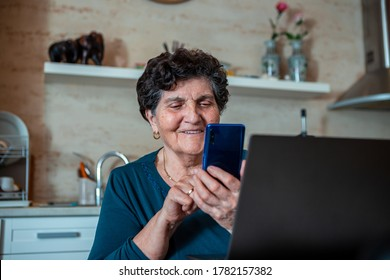 An older senior woman with black short hair is sitting in the dining room laughing and looking at the smartphone that is in her hand. It is located in front of the laptop.