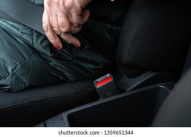 Older senior woman fastens a safety belt in a car wearing green and yellow jacket