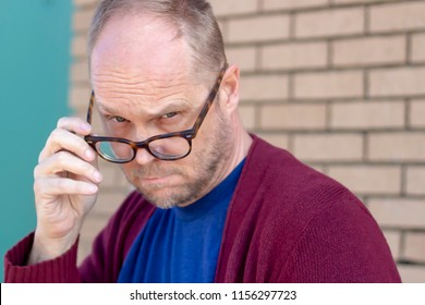 Older serious middle aged dad man wearing a cardigan looking down his nose over his glasses making eye contact directly at camera, disapproval judgement concept, horizontal shot