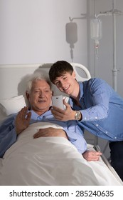 Older sick man and his grandson and video conference online