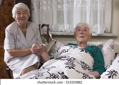 Older sick woman at home and her friend's visit