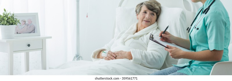 Older sick woman in hospital bed and her nurse