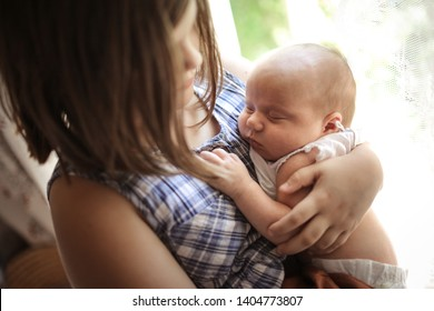 Older sister with a baby for 1 month, a girl hugging a newborn baby. Sibling care and love concept