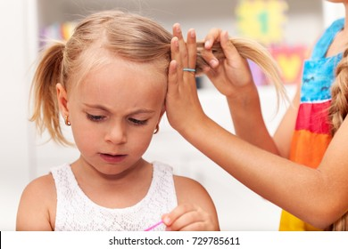 Older sister helps little girl tie her hair in plaits while playing, shallow depth