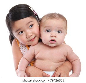 Older sister holding cute baby brother isolated over white