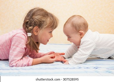 Older sister holding hands of her little sibling. Children lying on their tummies on the bed. Both laughing and having fun together. Side view.