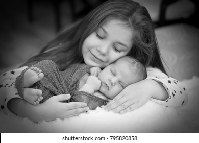 Older sister kwith her newborn brother. Sister love. (black and white)