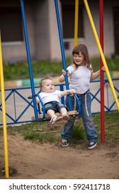 Older sister on  swing little sister, street, playground, help