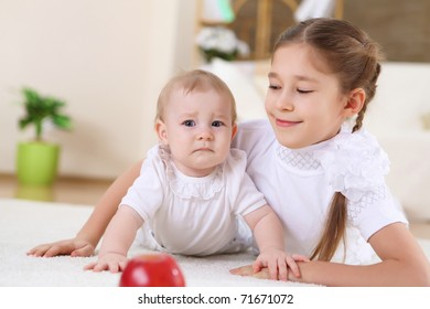 an older sister playing with a toddler sister at home