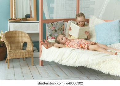 Older sister reading book to her younger sister