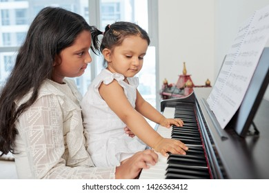 Older sister sitting together with her younger sister and teaching her to play the piano