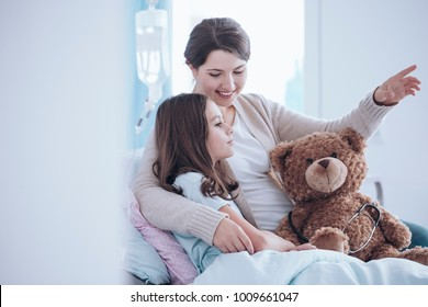 Older sister taking care of a sick child lying in a hospital bed with teddy bear