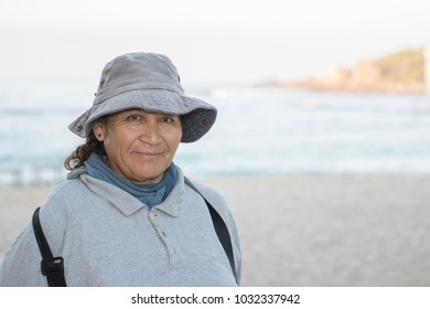 Older Smiling & Friendly Mexican Woman Working on a Resort Beach Raking and Cleaning up the Sand