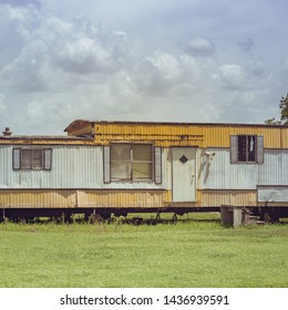 An older style mobile home, 1940's - 1970's, yellow and white metal walls with a built-in roof that is elevated, located in the center of the mobile home, in South Louisiana.