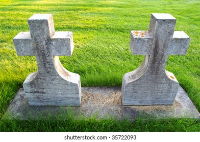 Older twin grave stones at a small town cemetery.