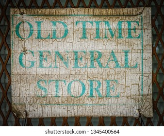 A older weathered worn Old time General store sign. This phot was taken in Louisiana.