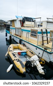 An older, well maintained house boat with inflatable dingy with an outboard motor on calm waters in marina at Fishermen's Terminal in Seattle, Washington