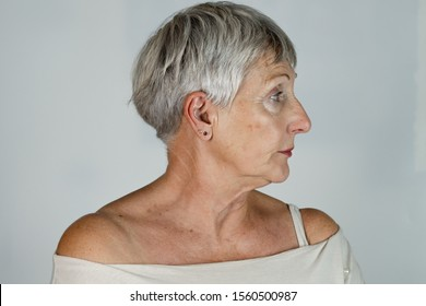 older White haired woman with White t shirt in profile on White background