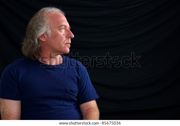 An older white male is looking towards copy space in blue t shirt against black background.