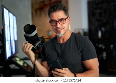 Older white man photographer in glasses at home holding photo camera and smart phone, smiling,