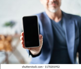 Older white man showing smart phone with blank screen.